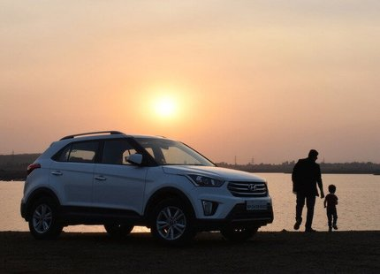 Father and son standing next to a white Hyundai SUV looking out at the water